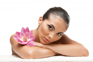 Young beautiful woman relaxing with lotus flower at spa isolated