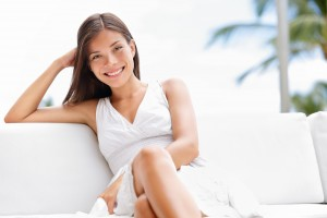 Portrait of young happy confident asian woman sitting outside in