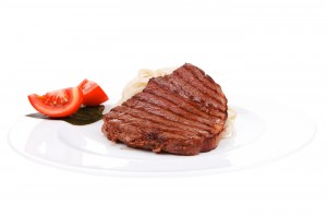 italian cuisine : grilled beef steak with pasta and tomatoes on